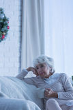 Ensam hög kvinna på soffan arkivfoto