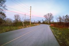 Ensam krökning av en lantlig väg på skymning arkivfoton