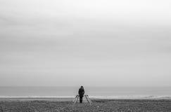 Ensam kvinna i röd klänning i träpir på stranden med det lugna havet Royaltyfri Bild