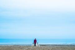 Ensam kvinna i röd klänning i träpir på stranden med det lugna havet Arkivbilder