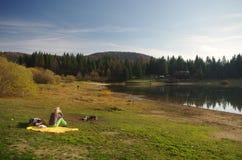 Ensam kvinna med ett picknicksammanträde vid sjön royaltyfria foton