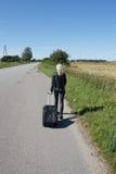 Ensam kvinna med resväska Arkivbild