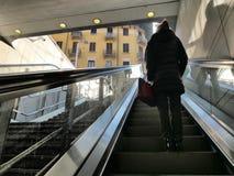Ensam kvinna på rulltrappabaksidasikt arkivbild