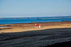 Ensam kyrka som är främst av havet i Island royaltyfri bild
