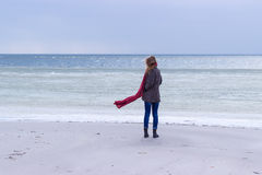 Ensam ledsen härlig flicka som promenerar kusten av det djupfrysta havet på en kall dag, rubella, höna med en röd halsduk på hals Royaltyfria Foton
