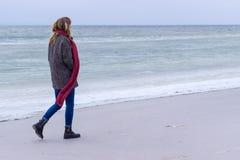 Ensam ledsen härlig flicka som promenerar kusten av det djupfrysta havet på en kall dag, rubella, höna med en röd halsduk på hals Arkivbild