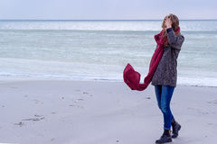 Ensam ledsen härlig flicka som promenerar kusten av det djupfrysta havet på en kall dag, rubella, höna med en röd halsduk på hals Arkivbilder