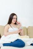 Ensam lycklig kvinnlig modell med cellphonelsammanträde på säng med bla Royaltyfri Fotografi