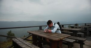 Ensam man i bergen Den unga stiliga mannen ligger hans huvud på armarna som sitter på tabellen med stor sikt omkring stock video