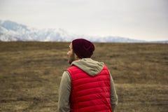 Ensam man i röd waistcoat som går in mot bergbakgrund fotografering för bildbyråer