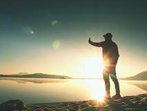 Ensam man på sjösidan genom att använda mobiltelefonen för att ta selfiefotoet med stranden bak honom royaltyfri bild