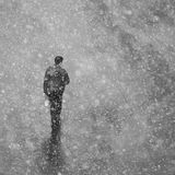 Ensam man som går på gatan i snö En man i ett omslag går royaltyfri fotografi