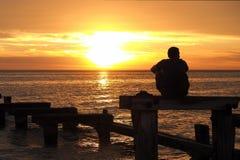Ensam man som håller ögonen på solnedgången på port Philip Bay Royaltyfri Foto