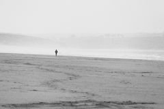 Ensam person som går på stranden i avståndet till och med misten Arkivbilder