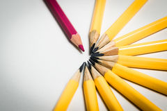 Ensam röd blyertspenna mot en grupp av gula blyertspennor Arkivbilder