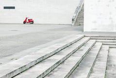 Ensam röd sparkcykel mot den vita väggen i stads- miljö arkivfoton