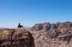 Ensam ryttare som ser över en kanjon fotografering för bildbyråer