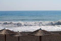 Ensam sandig strand med några sugrörsolparaplyer royaltyfri bild