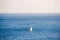 Ensam segelbåt i det öppna havet royaltyfri fotografi