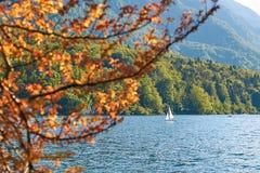 Ensam segelbåt på höstsjön i berg arkivbild