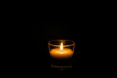 Ensam stearinljus på svart Fotografering för Bildbyråer