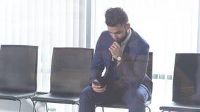 Ensam stilig man i modedräkten som sitter med smartphonen lager videofilmer