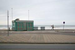 Ensam surfare i neoprenebaddräkt som går på trottoar t Arkivbild