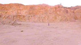 Ensam ung kvinna som barfota går på sanden i bakgrunden av bergen flyg- sikt arkivfilmer