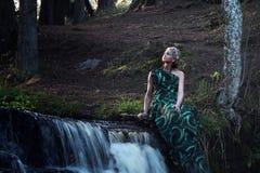 Ensam ung nymfkvinna nära vattenfallet i skogen Fotografering för Bildbyråer