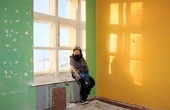 Ensam ungeflicka i övergiven gammal barnskola, äldre väggar med gula blåa gröna väggar för sprucken målare, lämnad kvar konstig v royaltyfri fotografi