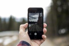 Ensam väg som igenom ses en iphone royaltyfria bilder