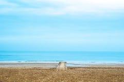 Ensam wood pir under molnig dag med det lugna havet och tyst himmel för blått Arkivfoto