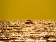 Ensam yacht på solnedgången royaltyfri bild