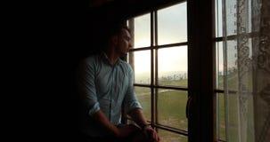 Ensamhet i bergen Den stiliga unga mannen ser ledset anseende för ett fönster och en hållande ögonen på episk solnedgång över stock video