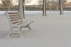 Ensamhet och parkerar bänken med tom snö Arkivfoto