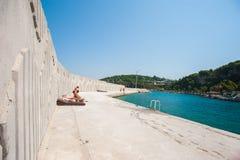 Ensamhet vilar in, dagdrivaren på betong nära havet arkivfoton