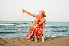 Ensamhetkvinna på stranden Fotografering för Bildbyråer