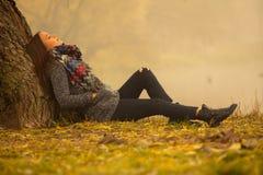Ensamma kvinnan som den har, vilar under trädet nära vattnet i en dimmig höstdag arkivbild