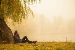 Ensamma kvinnan som den har, vilar under trädet nära vattnet i en dimmig höstdag arkivfoto