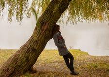 Ensamma kvinnan som den har, vilar under trädet nära vattnet i en dimmig höstdag royaltyfri bild