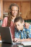 Ensamstående mamman och hennes tonåriga son arbetar på datoren Royaltyfria Foton