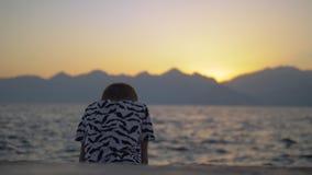 Ensamt barn på stranden på solnedgången lager videofilmer