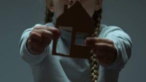 Ensamt barn som visar pappdiagramet av huset, flicka som drömmer om infött hem stock video