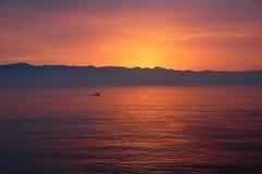 Ensamt fartyg i solnedgången av Ensenada Mexico arkivfoton