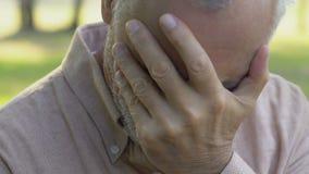 Ensamt gamal mansammanträde parkerar in och bitterly att gråta som stänger framsidan med händer lager videofilmer