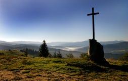 Ensamt kors under ett bergmaximum royaltyfri fotografi