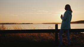 Ensamt kvinnadrinköl från en can på sjön Stående bara av staketet som ser solnedgången stock video