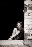 Ensamt liten flickasammanträde mot väggen Arkivbild