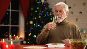 Ensamt manligt sammanträde nära att moussera Xmas-trädet som har champagne på julhelgdagsafton stock video
