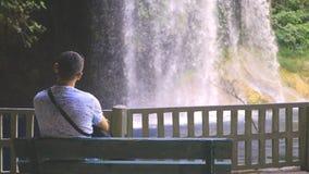Ensamt mansammanträde på en bänk i parkera med vattenfallet arkivfilmer